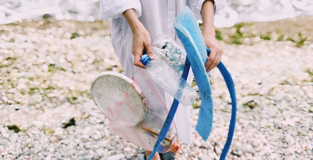 A person is cleaning up plastic waste from the beach.