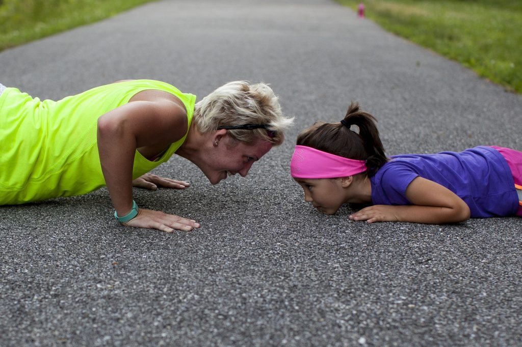 An older woman and a young girl doing pushups together