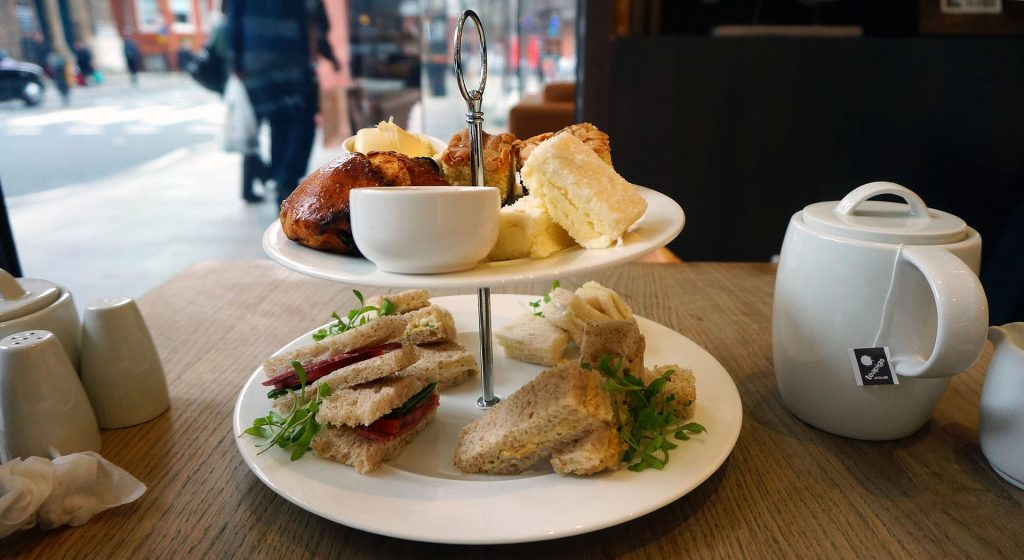 afternoon tea with sandwiches, cakes, biscuits and tea