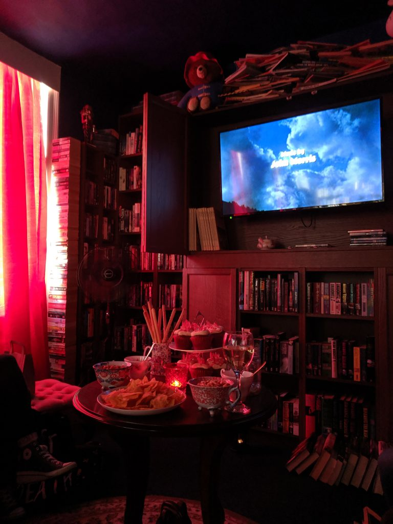 a dimly lit room filled with books, a movie is playing on a tv screen, and there's a table with snacks and wine