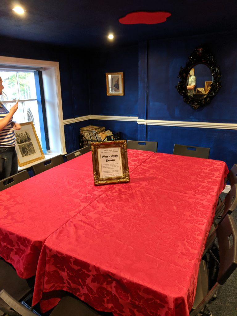 a table covered with a red velvet tablecloth, with a sign that says 'workshop room'