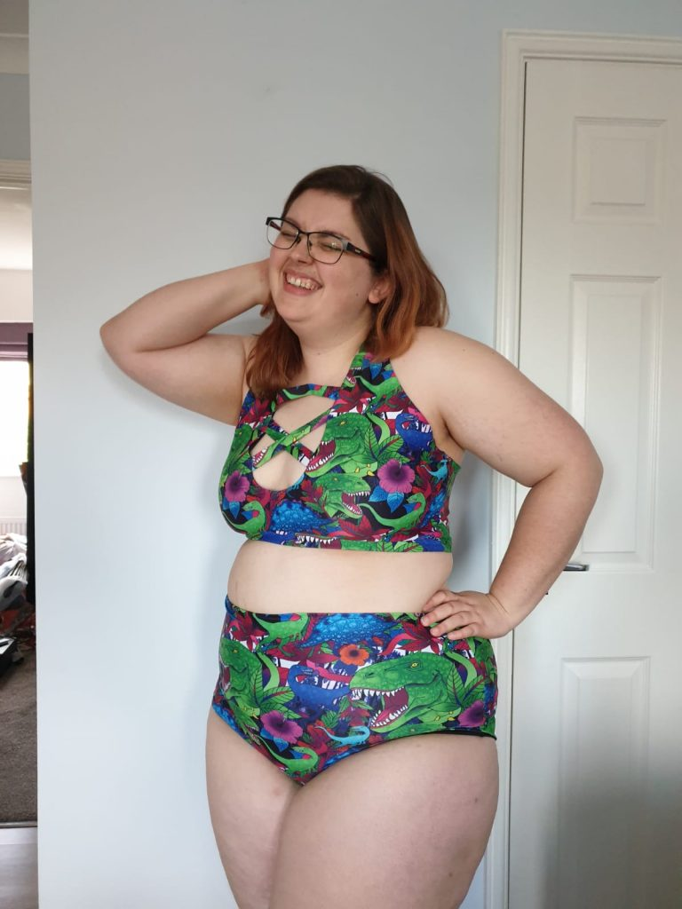 Emma is wearing Hoodlum Fang's lattice plunge crop top and high waisted cheeky shorts in dinosaurs and flowers fabric. She is laughing and has her hands on her hips.
