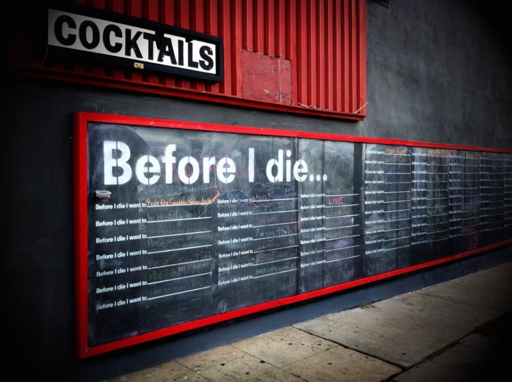 a chalkboard that reads 'before I die' and has space below for people to complete the sentence with their goals and aspirations