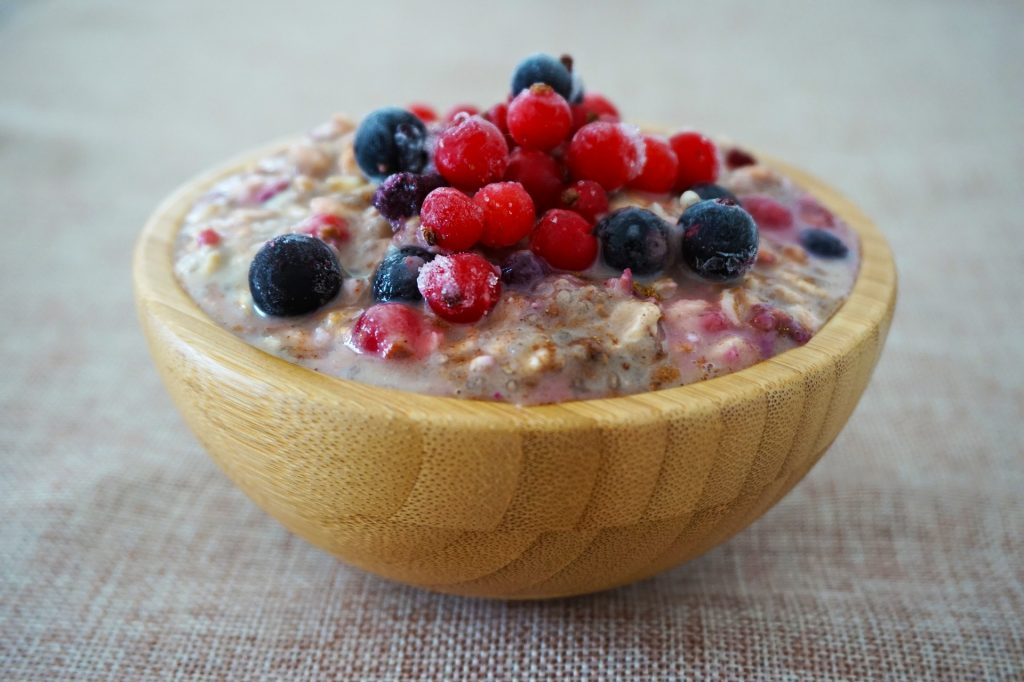 Porridge in a wooden bowl, topped with cranberries and blueberries.