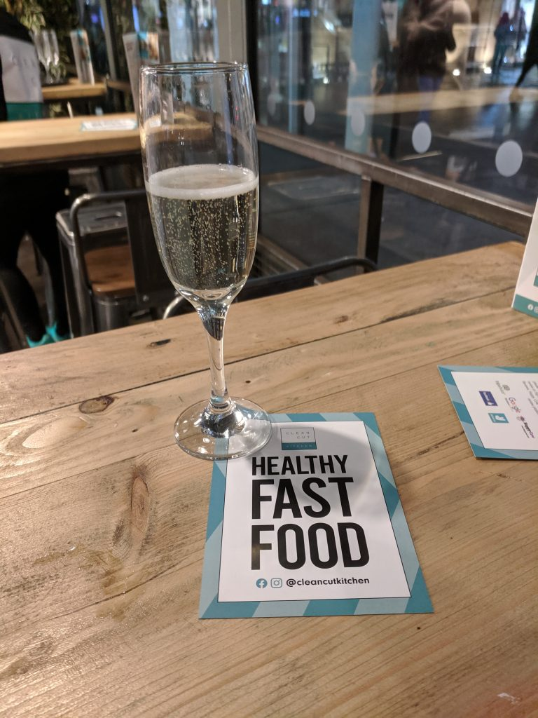 "A glass of prosecco next to a leaflet that says ""Healthy fast food"". They are on a wood table."
